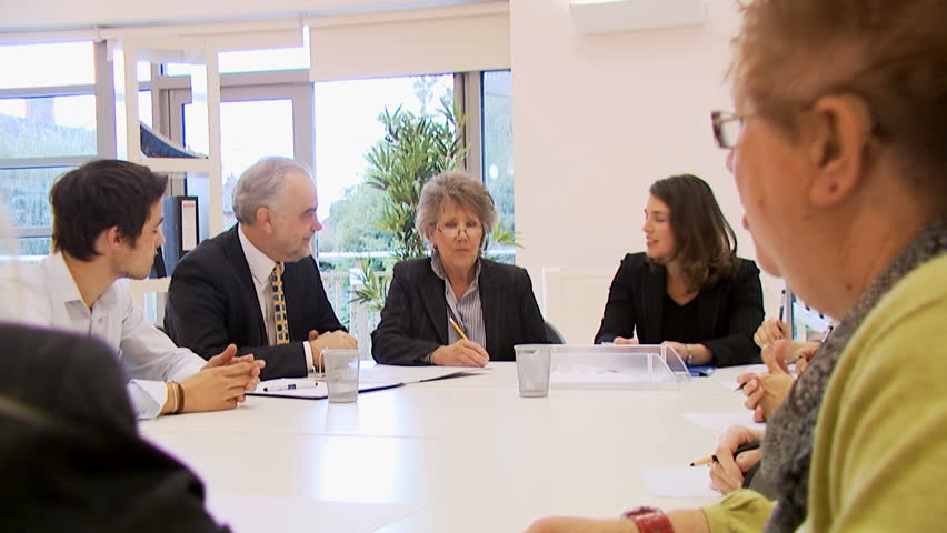 Diverse group of business people in a boardroom meeting, seated around a conference table. High quality HD video footage