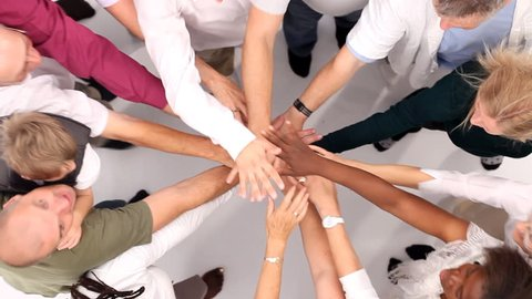 Group of people coming together and joining hands to form a happy close group of individuals. Shot from above in large white studio. High quality HD video footage