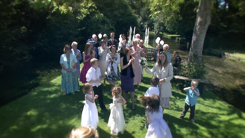 Bride throws her bouquet at happy summer outdoor wedding.