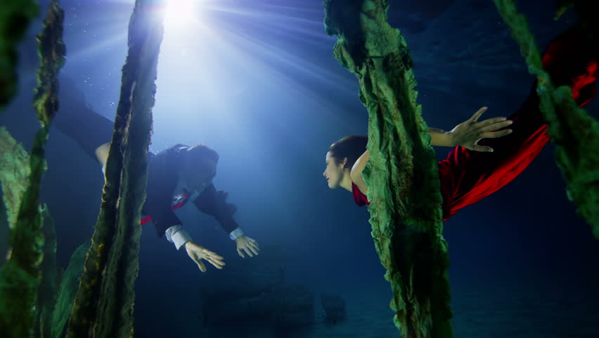 Beautiful underwater couple in elegant clothes swim to each other and kiss and embrace.