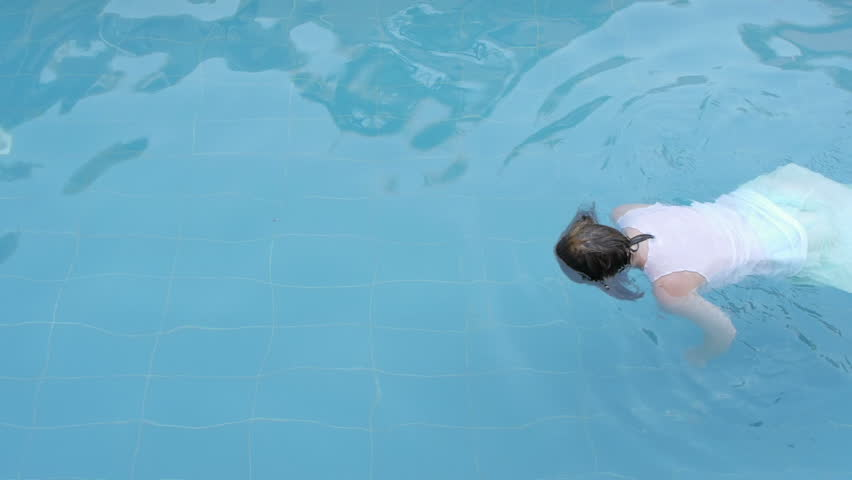 drowned woman body drifting in a swimming pool facing down