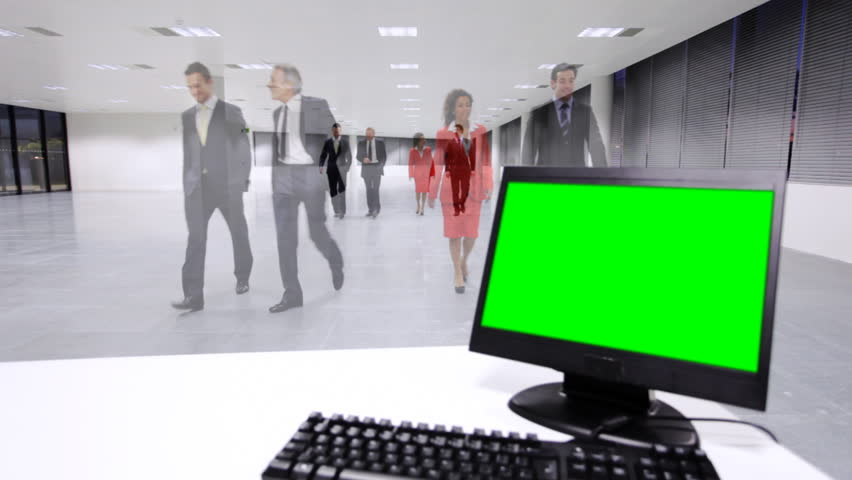 Confident and successful business team walking in a modern office building. Computer with green screen in the foreground.