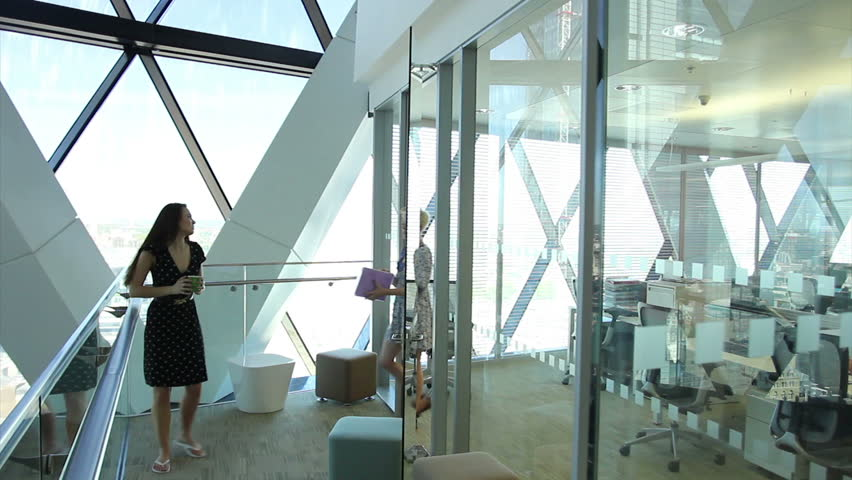 Confident and successful young business team working in a modern high rise office. Two women have a meeting in the hallway.