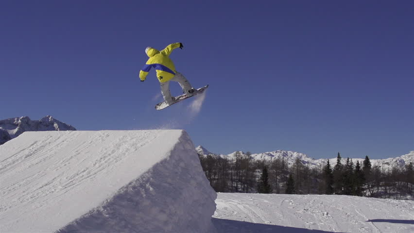 SLOW MOTION: Snowboarder jumping over a kicker in snow park