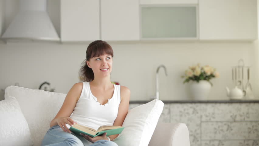 Attractive young woman sitting at table with book and smiling at camera