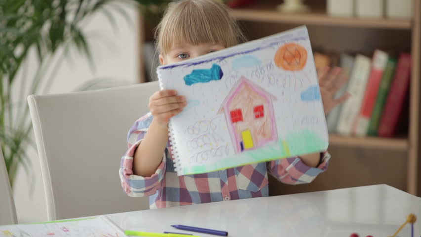 Cute little girl sitting at table drawing with colored pencils and showing her