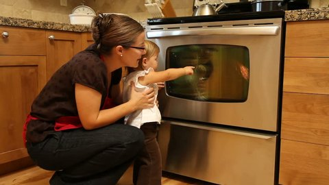 Mother and daughter looking at turkey in oven