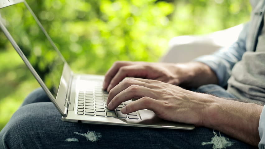 Male hands typing on laptop in the park