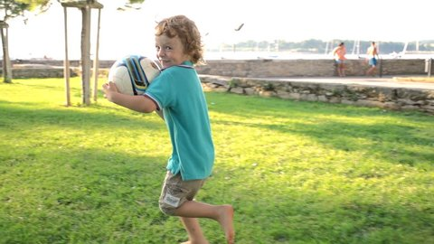 Slow Motion Shot Of A Cute Red-Haired Boy Holding A Ball, Running Away Over Green Grass And Smiling Happily