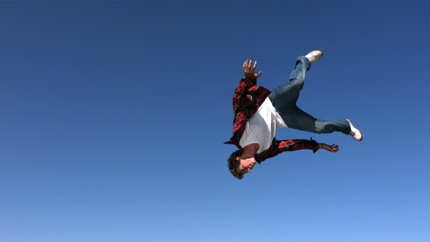 Teen boy flips in sky, slow motion