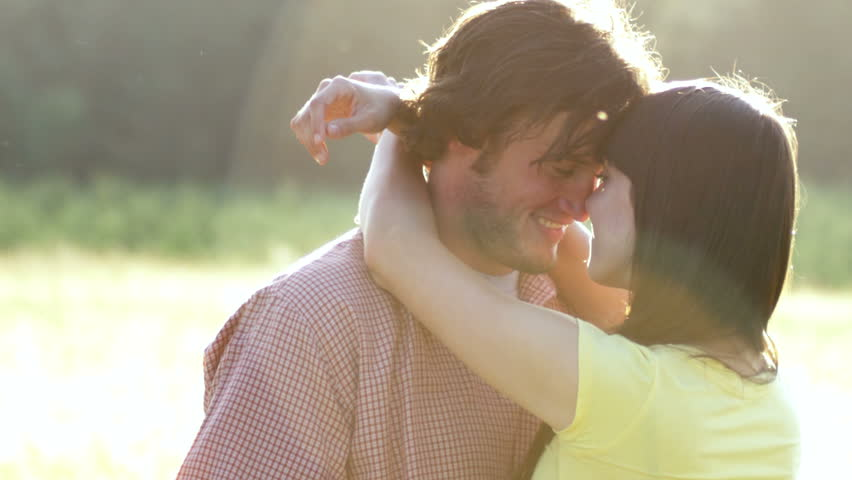 Beautiful Young Couple in Love kissing in a field in slow motion