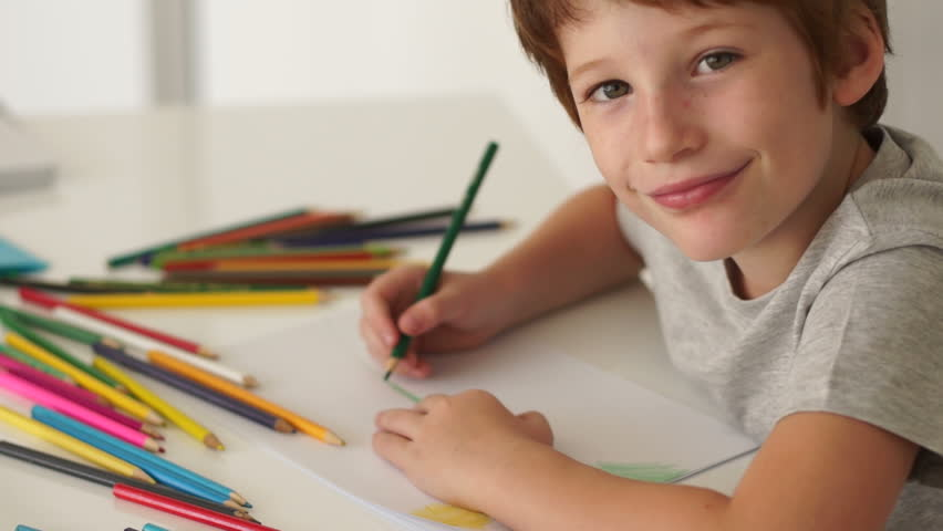 Little boy sitting at table and drawing with colored pencils