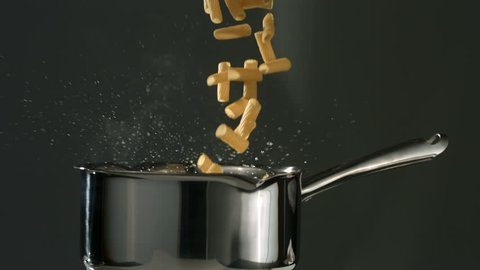Rigatoni pasta falling into boiling water, slow motion