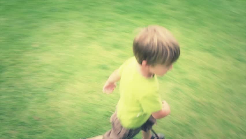 A little boy running on the grass at the park | Shutterstock HD Video #4603325