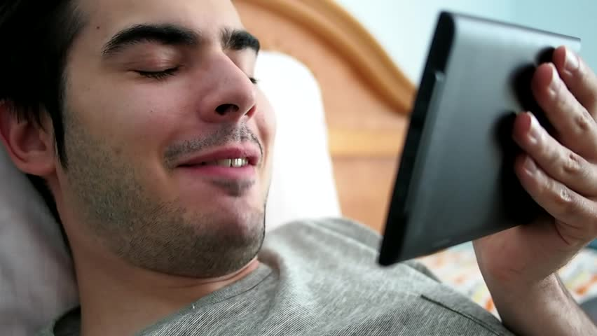 Man talks to somebody on a video call while in bed
