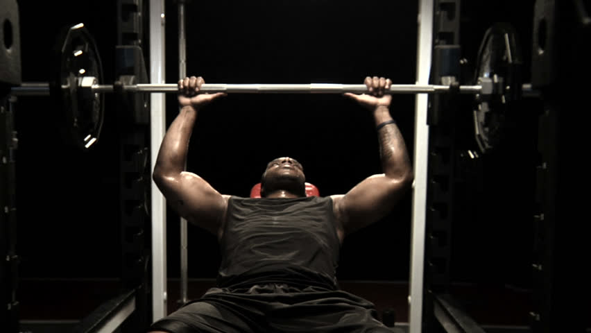 An athlete rests between bench press repetitions and looks into the camera | Shutterstock HD Video #4621970