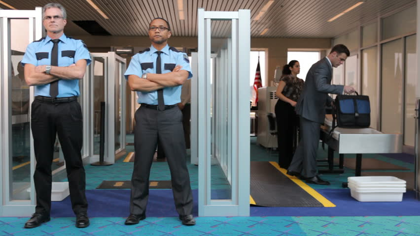 Two airport security guards standing in front of metal detector