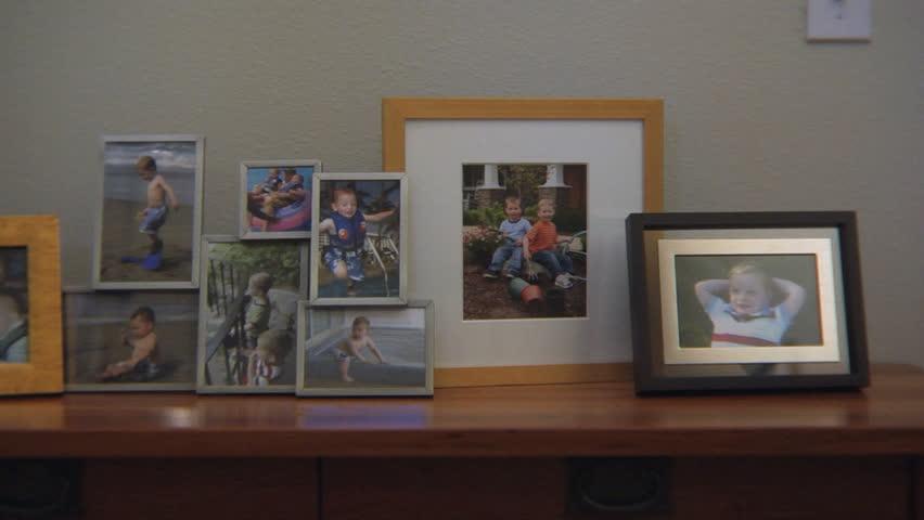 Framed family photos on a fireplace