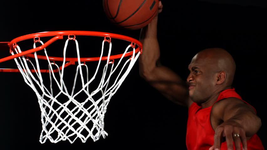 Basketball player slam dunks ball