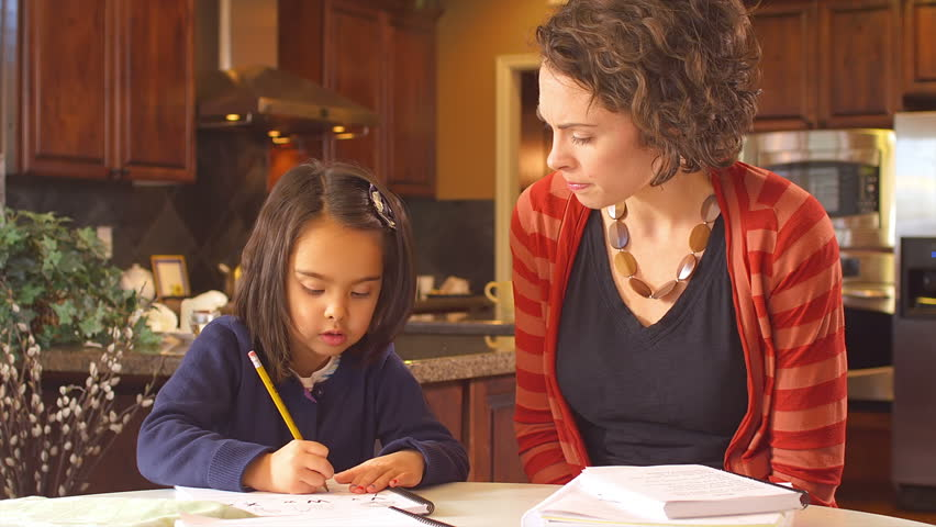 A mother sits at the kitchen table and assists her young daughter with her homework