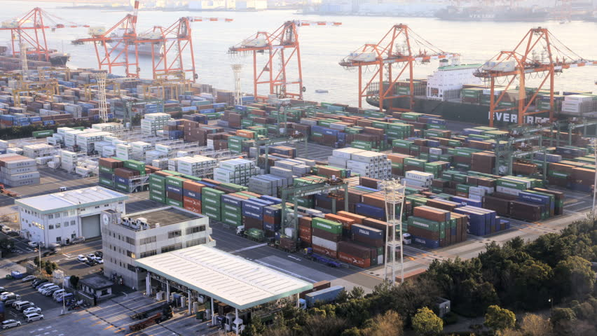 Japan - March 2011: Time lapse view of activity at a busy Japanese Cargo Container Port with the arrival of a commercial cargo ship in, Odaiba, Tokyo, Japan in March, 2011