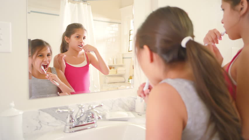 Two adorable little sisters share the bathroom as they brush their teeth and get ready for bed. Close up shot.