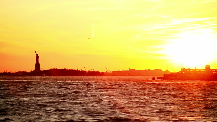 The sun is setting over the Statue of Liberty as a speed boat zooms by. Wide shot. | Shutterstock HD Video #4650920