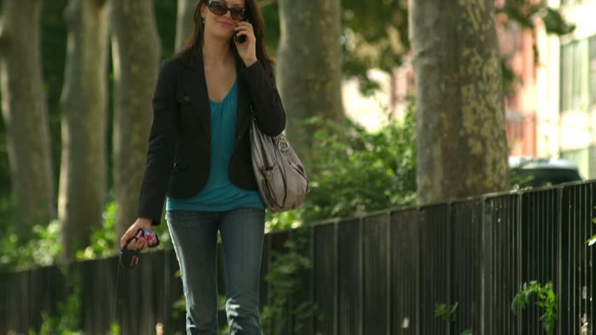 Woman walks her dog as she talks on her cell phone. Medium shot.