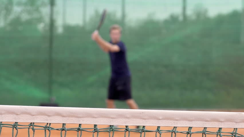Slow Motion Dolly Shot Of A Professional Tennis Player Playing Tennis. Focus On