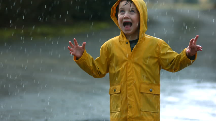 Young boy playing in rain, slow motion