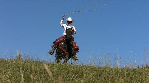 Cowboy rides over hill swinging lasso, slow motion