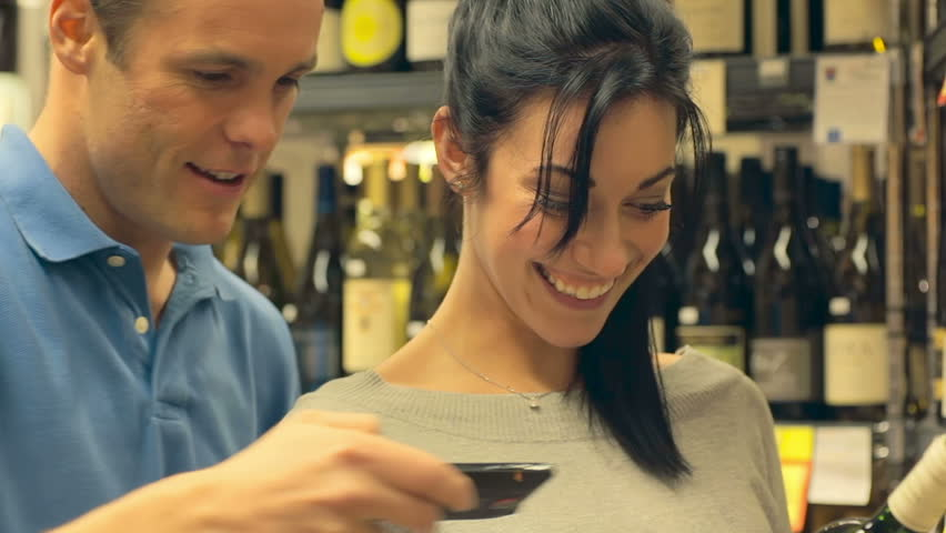 A couple uses a cell phone to look up different wines as they try to pick one out of many. Close up shot. | Shutterstock HD Video #4658336
