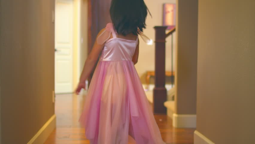 A cute little girl twirls and spins down the hallway. Medium slow motion shot.