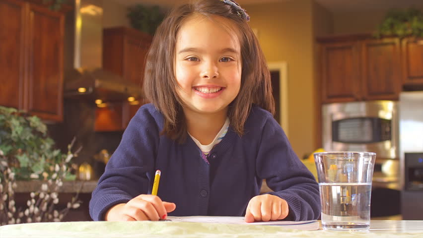 A funny little girl sits at the table and does her homework, then looks up and gives the camera a thumbs up and a thumbs down. Close up shot. | Shutterstock HD Video #4659080