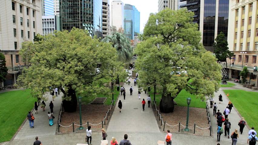 Commuters and pedestrians walk through Anzac Square between skyscrapers in central Brisbane, Queensland, Australia