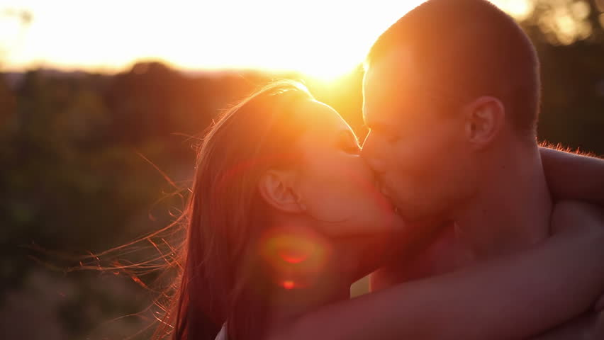 Passionate couple kiss as the sun sets. Medium shot.