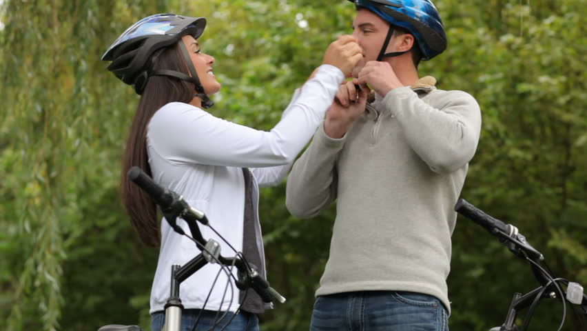 Couple putting on bicycle helmets