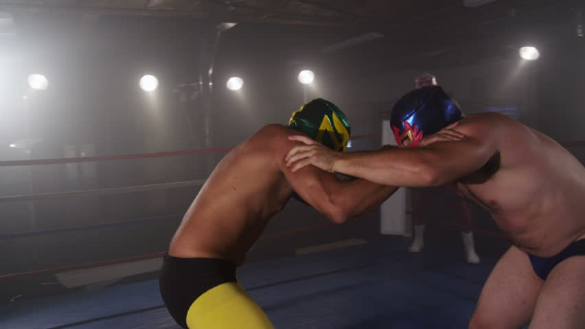 Masked wrestlers fighting in ring, slow motion