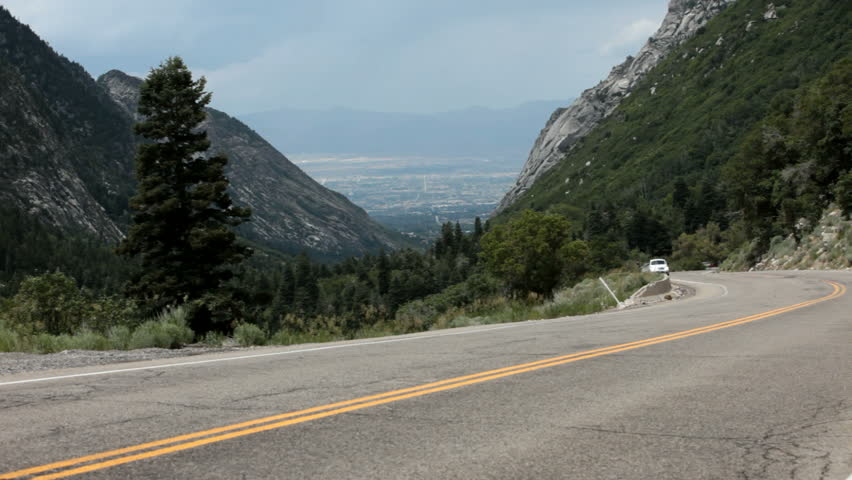 Cars driving on a mountain road. Forest and valley below. Wasatch Mountains above Salt Lake City, Utah.