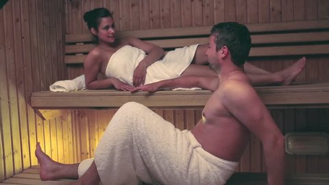Couple relaxing and chatting together in a sauna at the hotel spa
