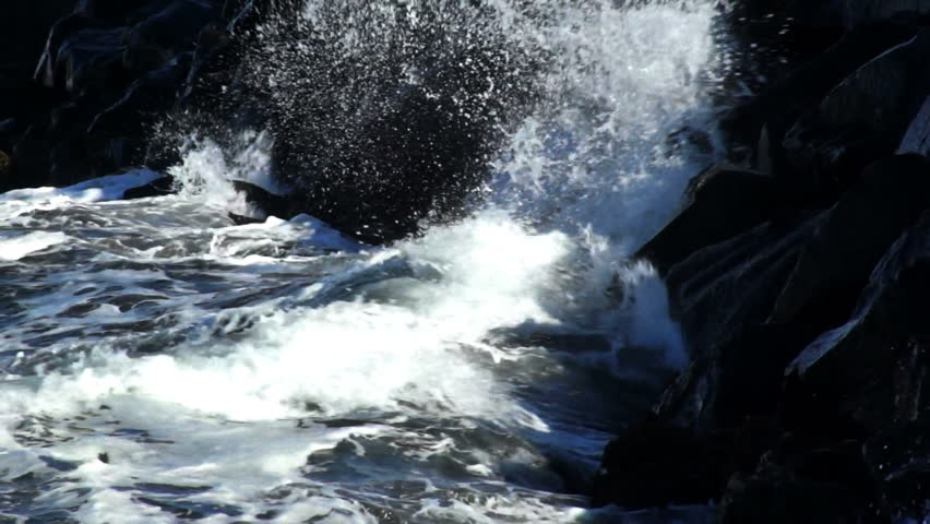 Iceland. Stormy sea waves on rocky beach near Reykjavik in late autumn. High contrast. Slow motion, close up.