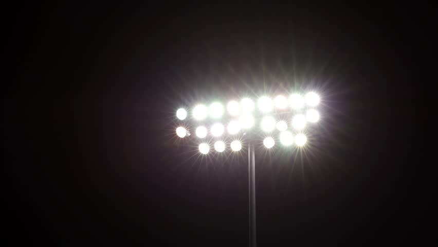 Isolated shot of stadium flood lights turning on a black sky background