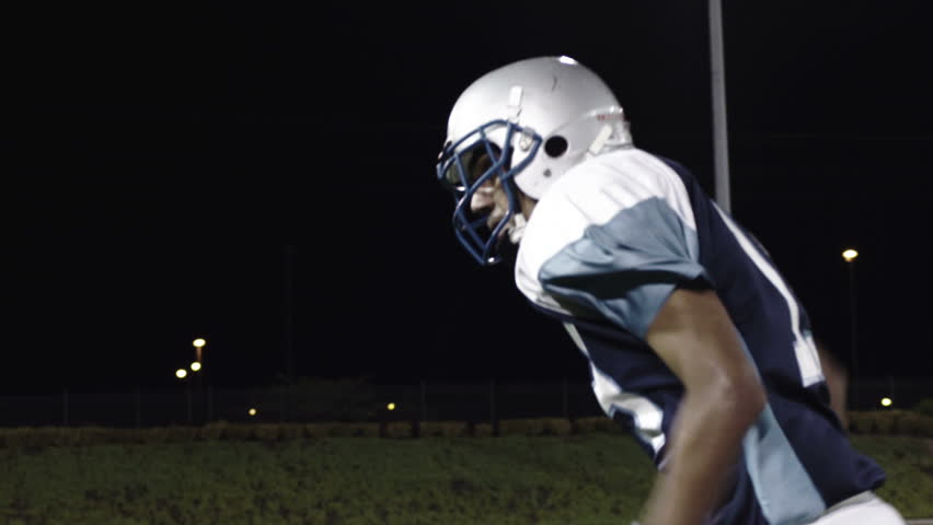A wide receiver watches the ball come towards him and catches it