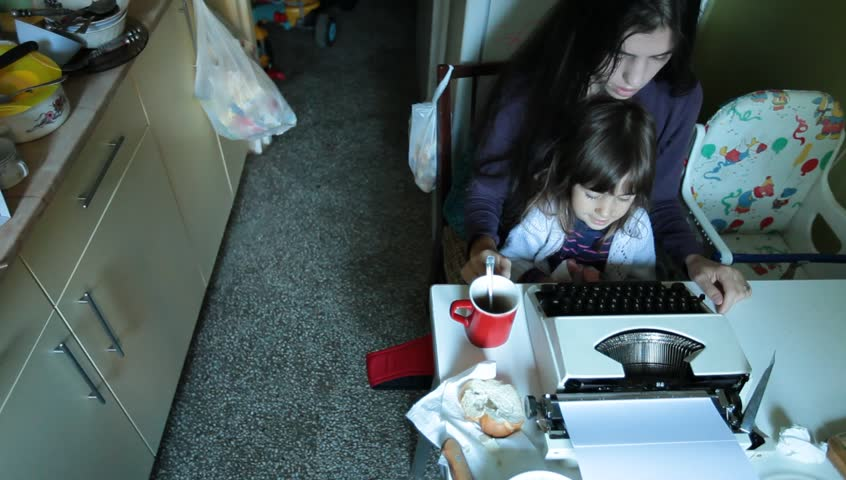 Mother with obsolete vintage typewriter typing in the kitchen and taking care of little baby girl child. Daylight urban indoor scene. Business, motherhood and childhood concept and idea..  | Shutterstock HD Video #4730840