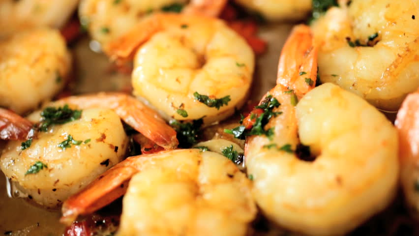 Close up of trasty fresh prawns with herbs browning in a saute pan in slow motion