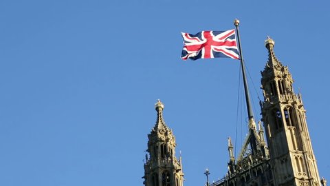 British flag on Palace of Westminster, Houses of Parliament in London, United Kingdom. The UK flag, Union Jack against clear blue sky.