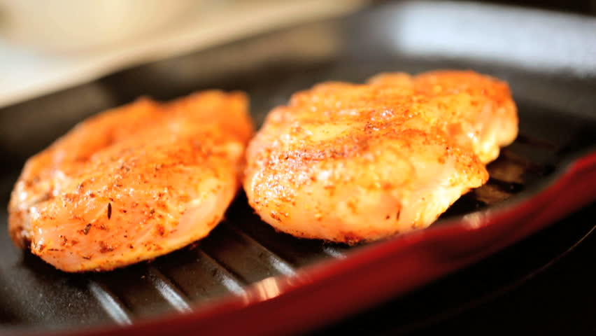 Close up of white meat chicken cutlers grilling on a griddle pan for a healthy balanced meal