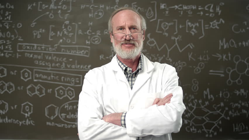 A college professor poses for a portrait with his arms crossed in front of a chalkboard full of equations