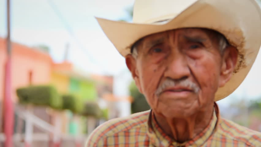 An older Mexican man in a cowboy hat at a market smiles and poses for the camera