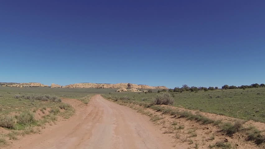 Drive desert road San Rafael Swell Utah POV point of view. Camera mounted outside of car. Vacation travel in southwestern. Dirt road San Rafael Swell. Exploring historic uranium mining roads trails.